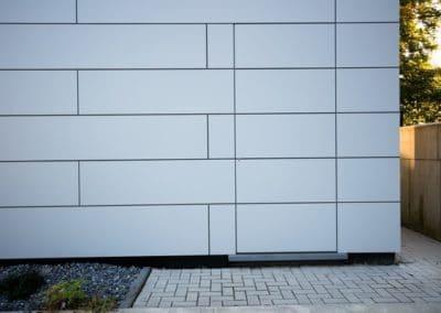 Porte invisible insérée dans des panneaux Trespa collés
