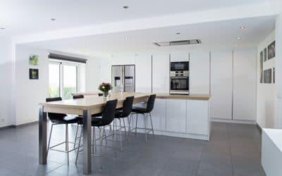 Aménagement complet d'une cuisine en stratifié blanc mat et plan de travail en chêne massif. Table haute avec allonge