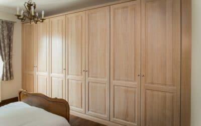 Dressing avec portes en chêne massif moulurées, finition cérusé blanc